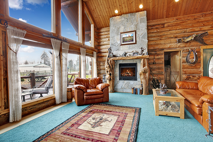 Large beautiful living room in log cabin house with stoned background fireplace, leather chair and couch.
